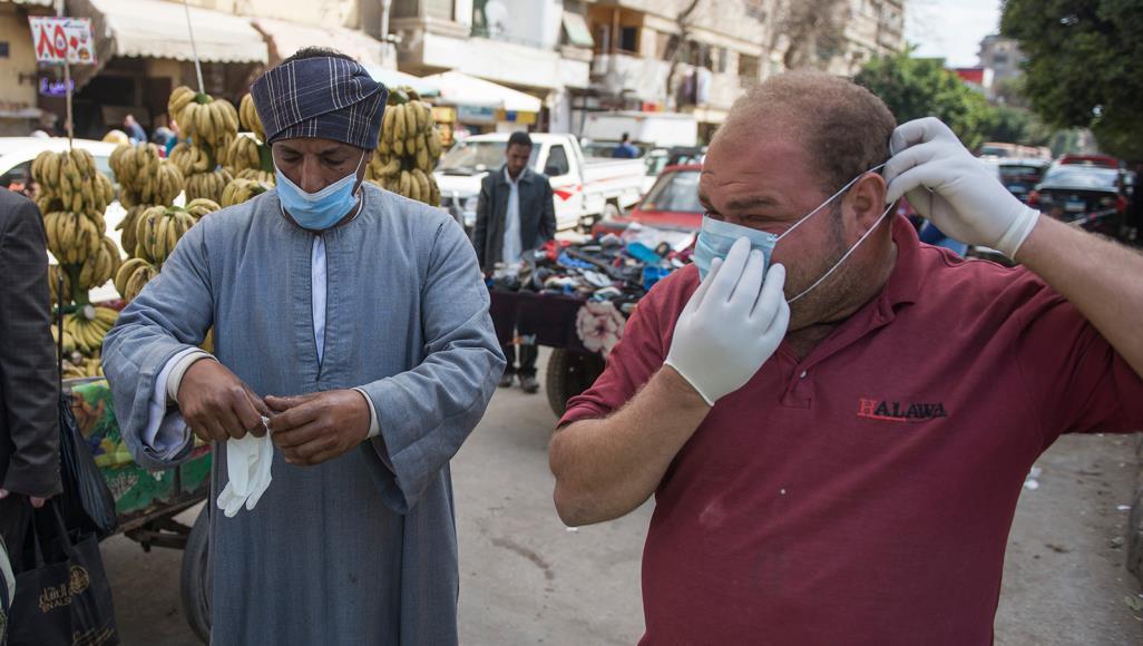 رجلان يرتديان أقنعة للوقاية من فيروس كورونا في أحد شوارع القاهرة (الأوروبية)